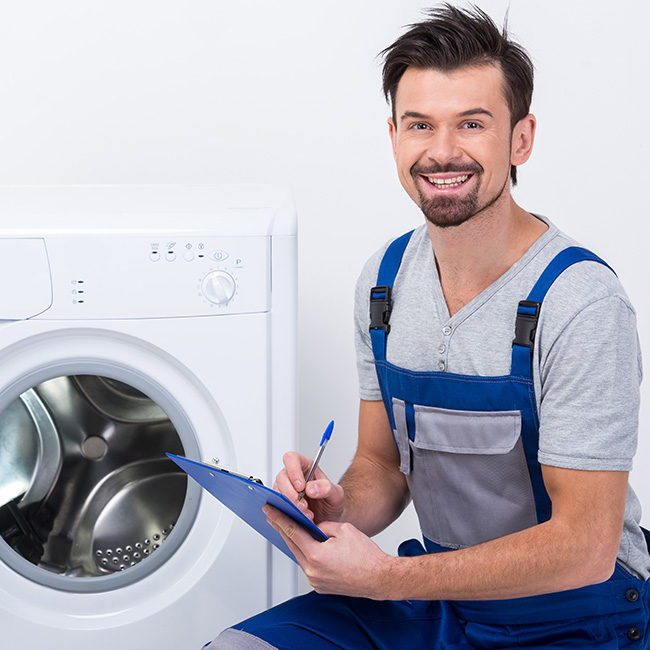 Repairman is repairing a washing machine for housewife